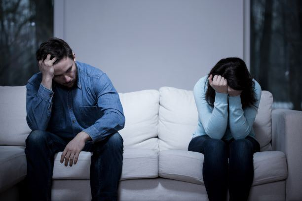 woman crying and man sitting with his head in his hands